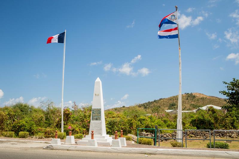 Bild: Grenzüberquerung auf der A. T. Illidge Road mit Border Monument von Belle Plaine/Poumou/Quartier d'Orleans, Saint-Martin nach Belvedere, Sint Maarten 🇸🇽