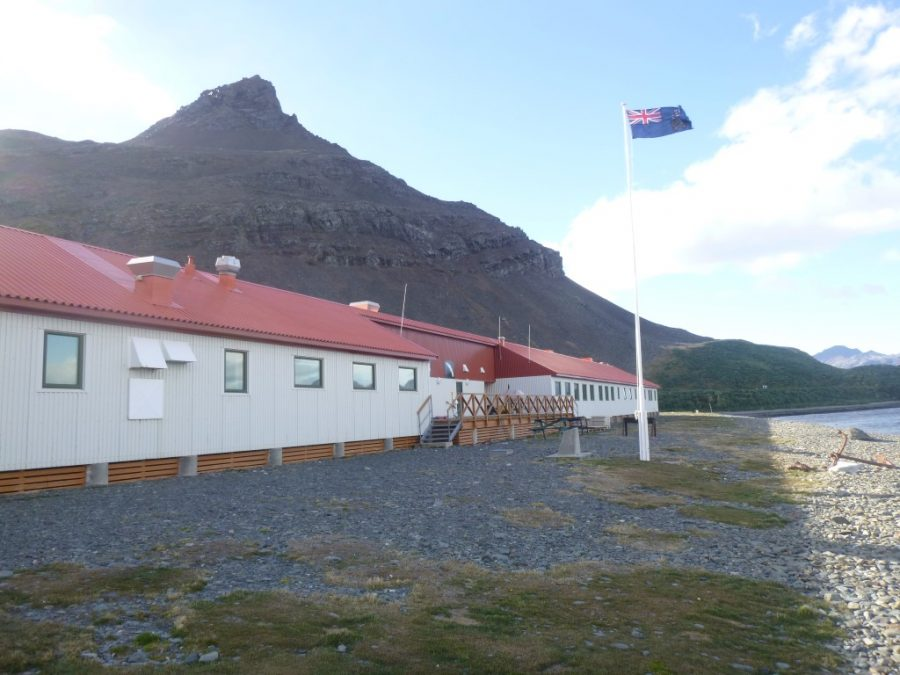 """Bild: gehisste Flagge von Südgeorgien und den Südsandwich-Inseln vor dem Everson-Haus in der Forschungsstation """"King Edward Point"""""""